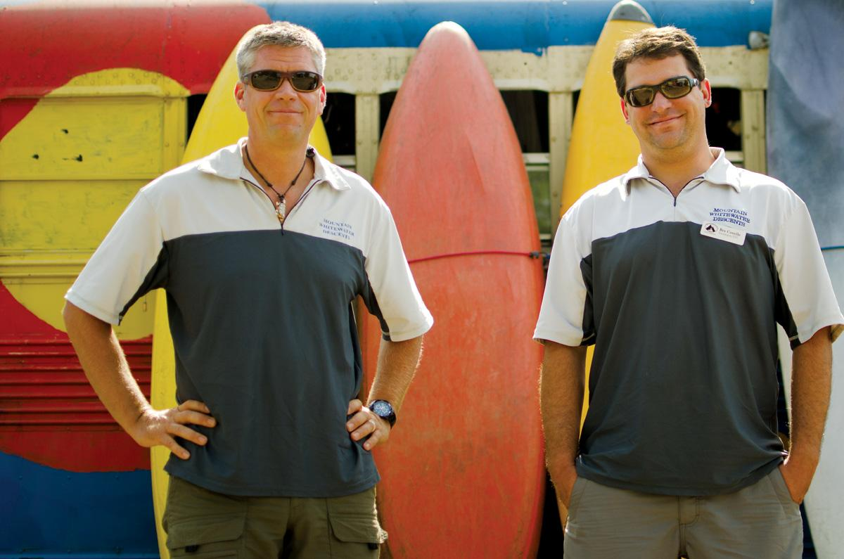 Brad Mosesitt, owner of Mountain Whitewater Descents, and Ben Costello, manager, stand in front of kayaks on their business' property. Mountain Whitewater Descents has had to close for the first time in its 12 year history due to the Hewlett Gulch and High Park Fires.