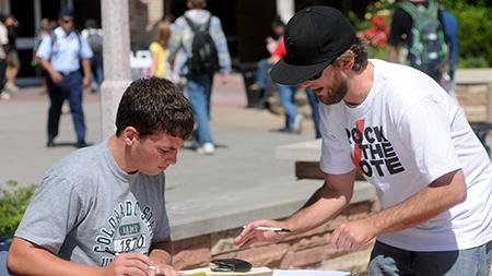 Kevin Kruglet, left, is assisted by voter registration volunteer Will Minton while filling out his Colorado voter registration form in 2010 on the Plaza outside of the Lory Student Center.