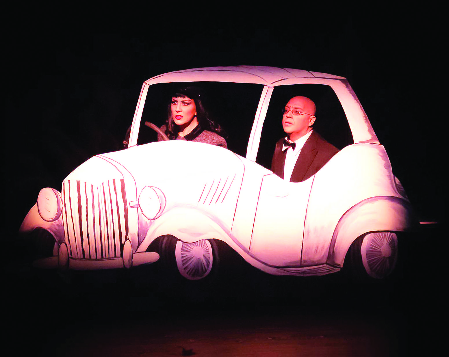 Ailie Holland as Lenya Von Brunno, left, and Justin Batson as Otto Von Brunno perform the car chase scene from Bullshot Crummond in the Lincoln Center. The play is a spoof off of a grade-B detective movies including a damsel in distress and car chases.