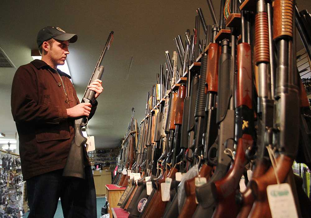 Wildlife Biology major Sam Peterson browses through the shotgun collection at the Rocky Mountain Shooter Supply off of Mulbery Tuesday afternoon. The store reports an increase in gun sales since the recent Sandy Hook shootings.