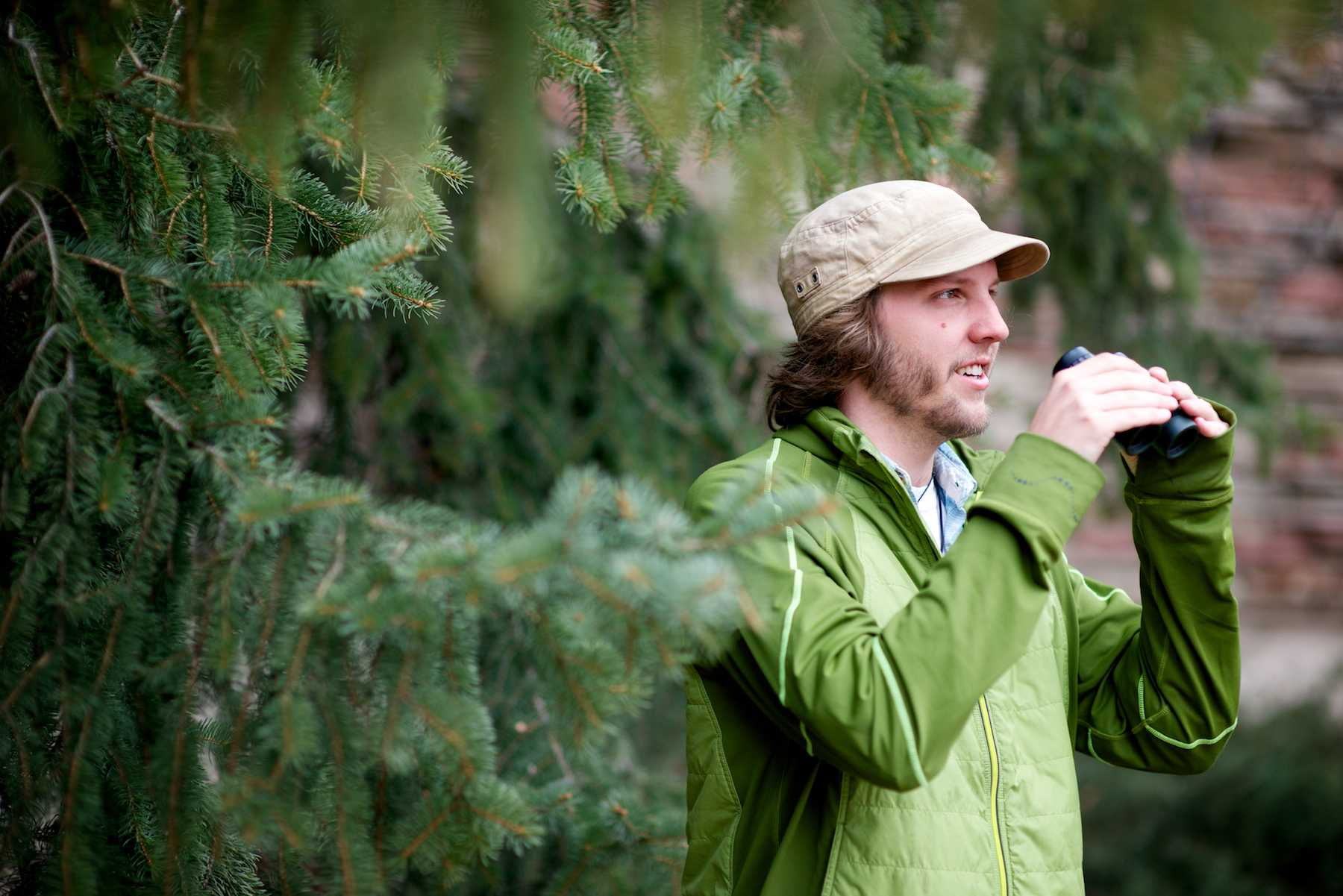 Adam miller, a senior wildlife biology major, uses binoculars to identify birds from their site and call in the Monfort Quadrangle. Miller has been involved in undergraduate research since freshman year and is currently studying how housing development affects bird nesting patterns.