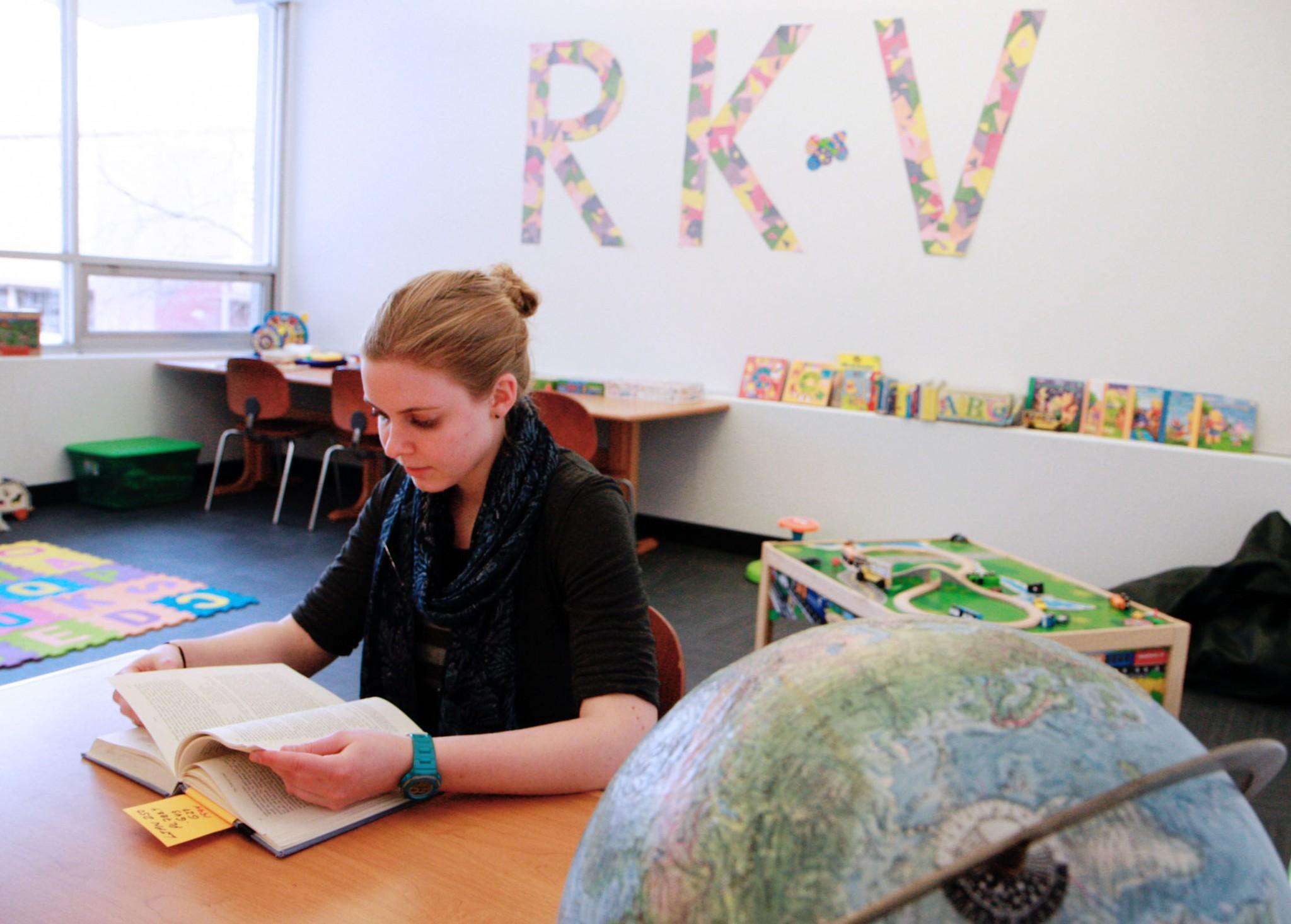 Rams Kids Village Activity Assistant, Bethany Hettinger, reads a library book as she waits for CSU student parents to drop their kids off. Started last semester, Rams Kids Village has seen an enrollment increase of eight families so far this spring and expects to see more.