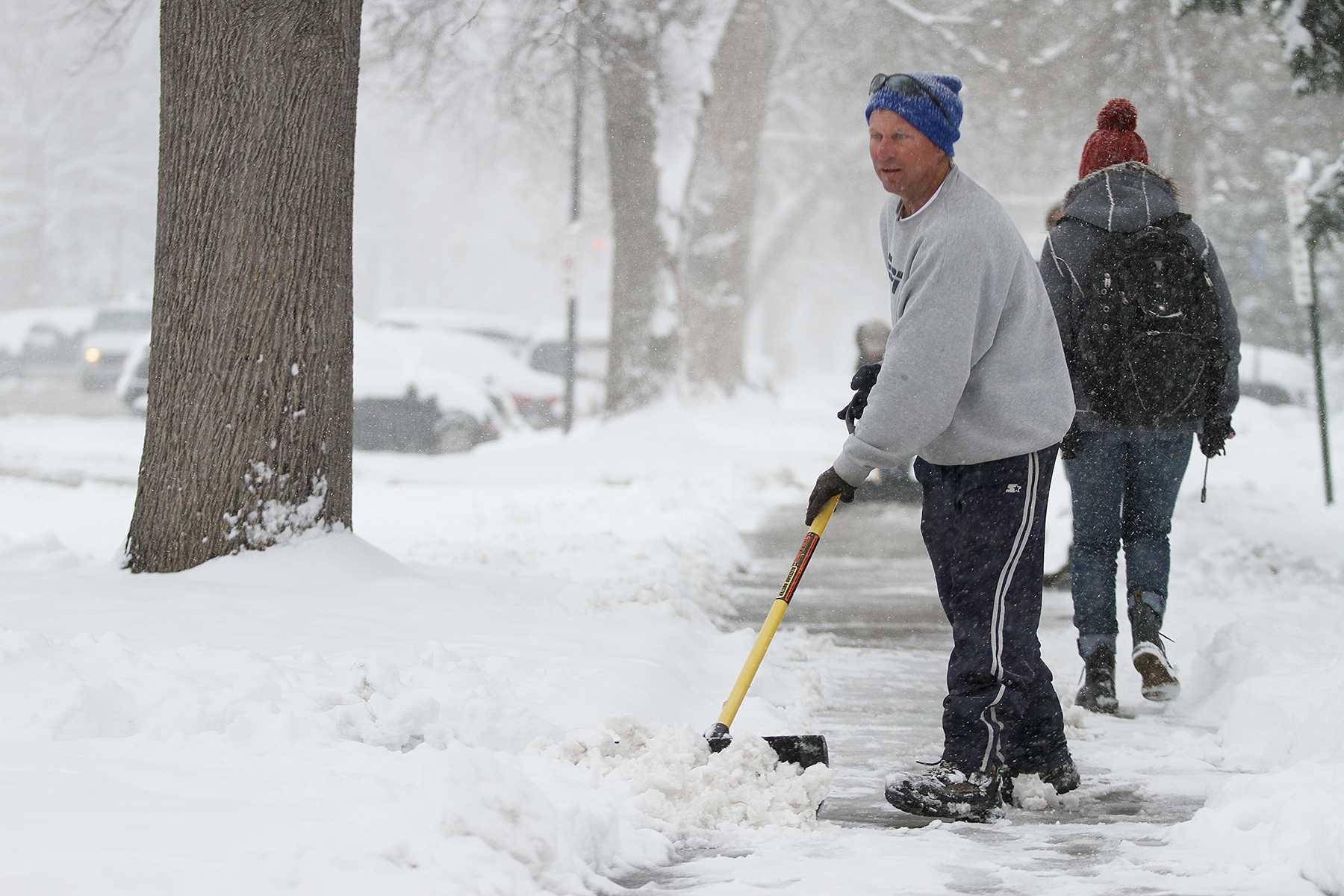 Dave Dean shovels snows off his sidewalk on Meldrum on Monday afternoon.