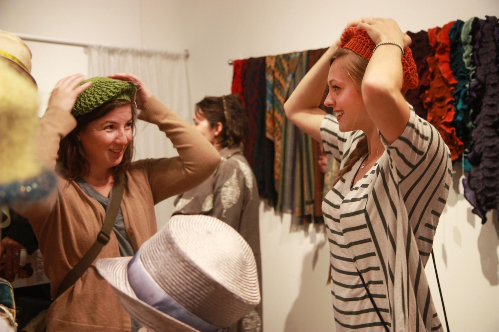 CSU art students, Leah Walker and Molly Wilson, try on hats made by local artists during the ArtWear Fashion show this past Friday. Walker helped set up for the event, held by the Lincoln Center, and was pleased to have something different and fun for her and a friend to do within the Fort Collins community.