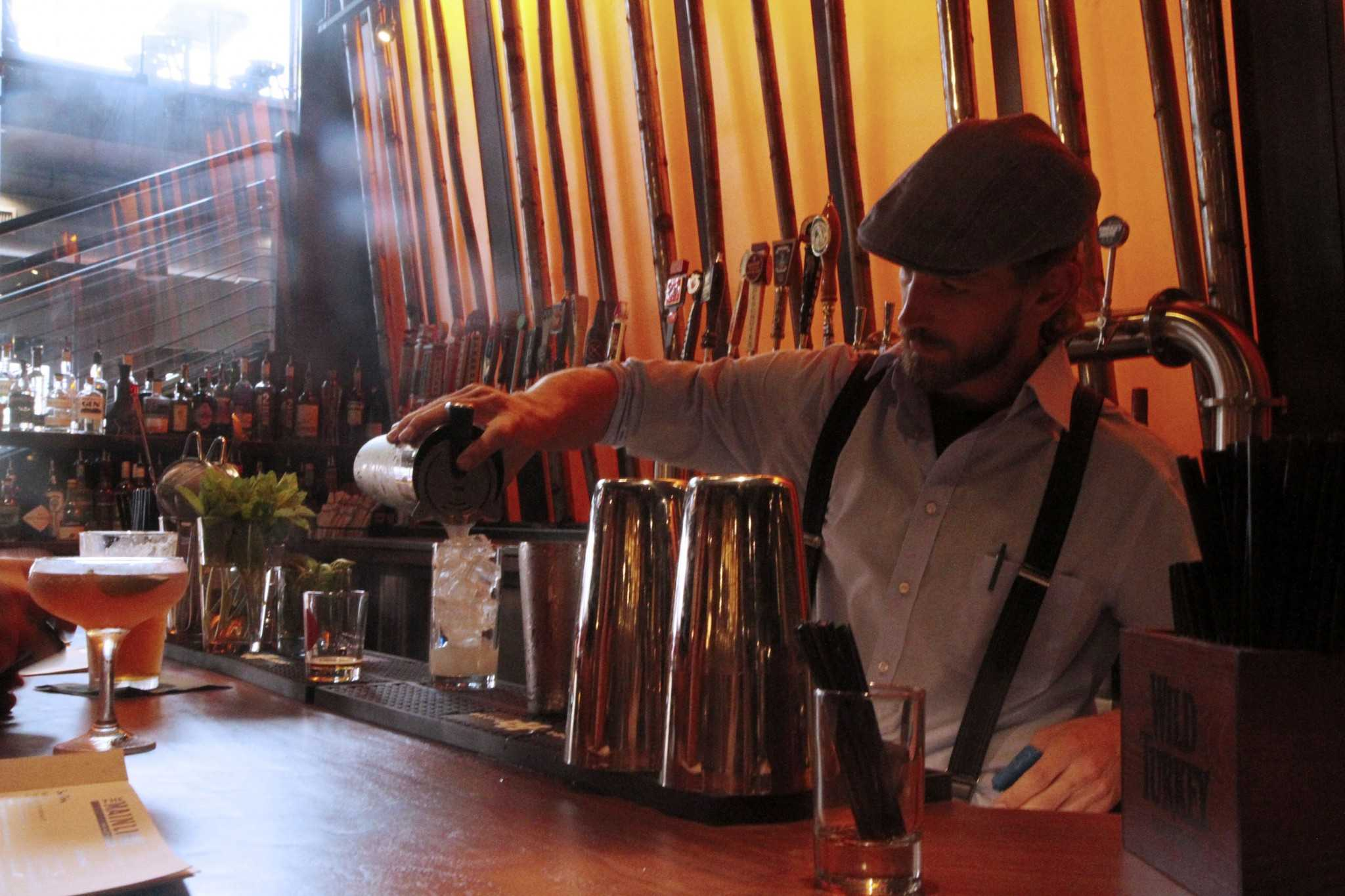 Mainline bartender pours drinks for afternoon customers. The Mainline staff is hospitable, friendly, and very welcoming to dinners.