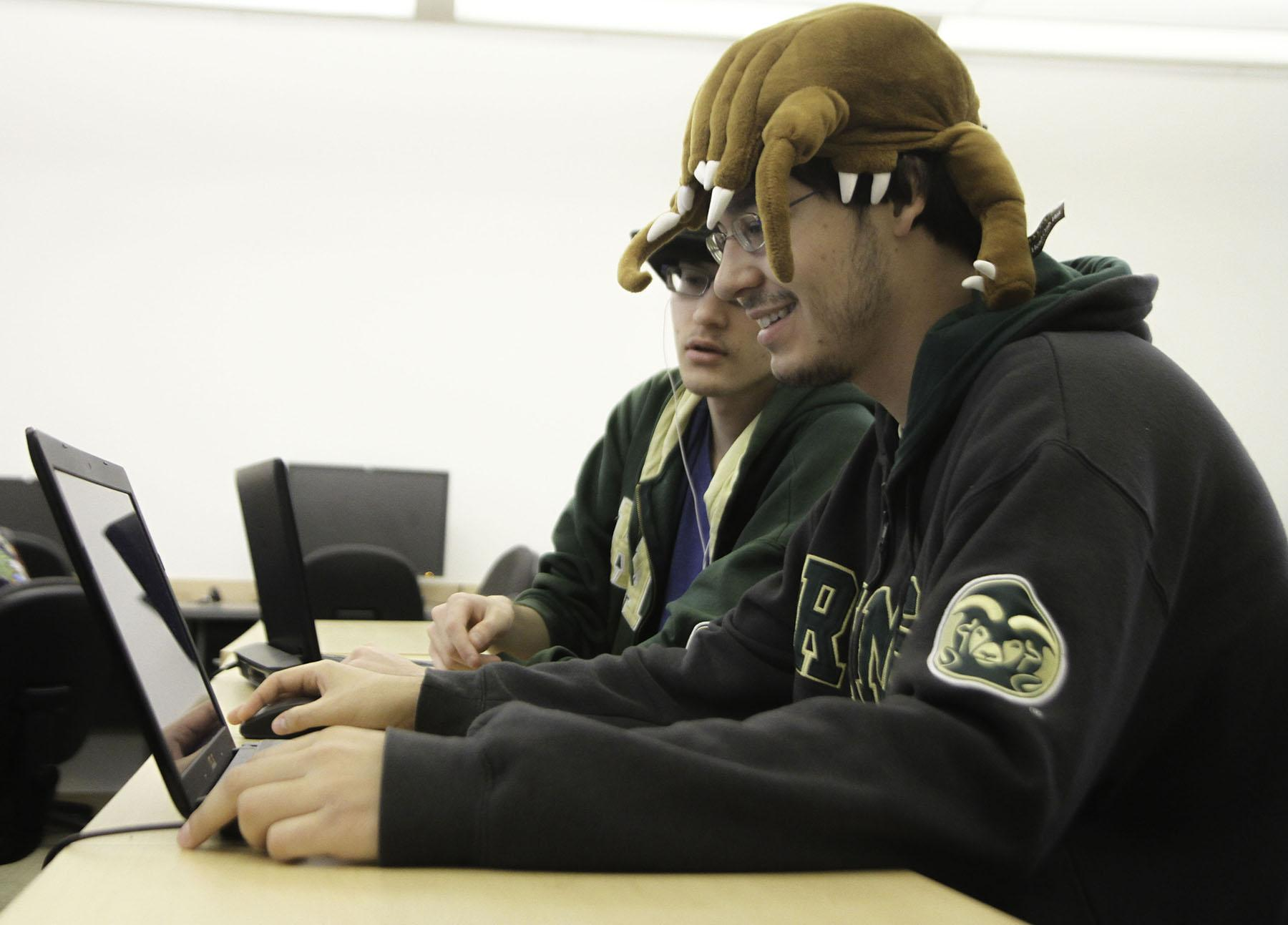 Ryan Stern (left) and his brother Jeff work in CS325 with their team to code a program within their eight hour allotted time limit that will fulfill certain criteria. A number of teams at CSU competed against each other and other international teams during Code Wars 2014 Windwardopolis 2 this Saturday.