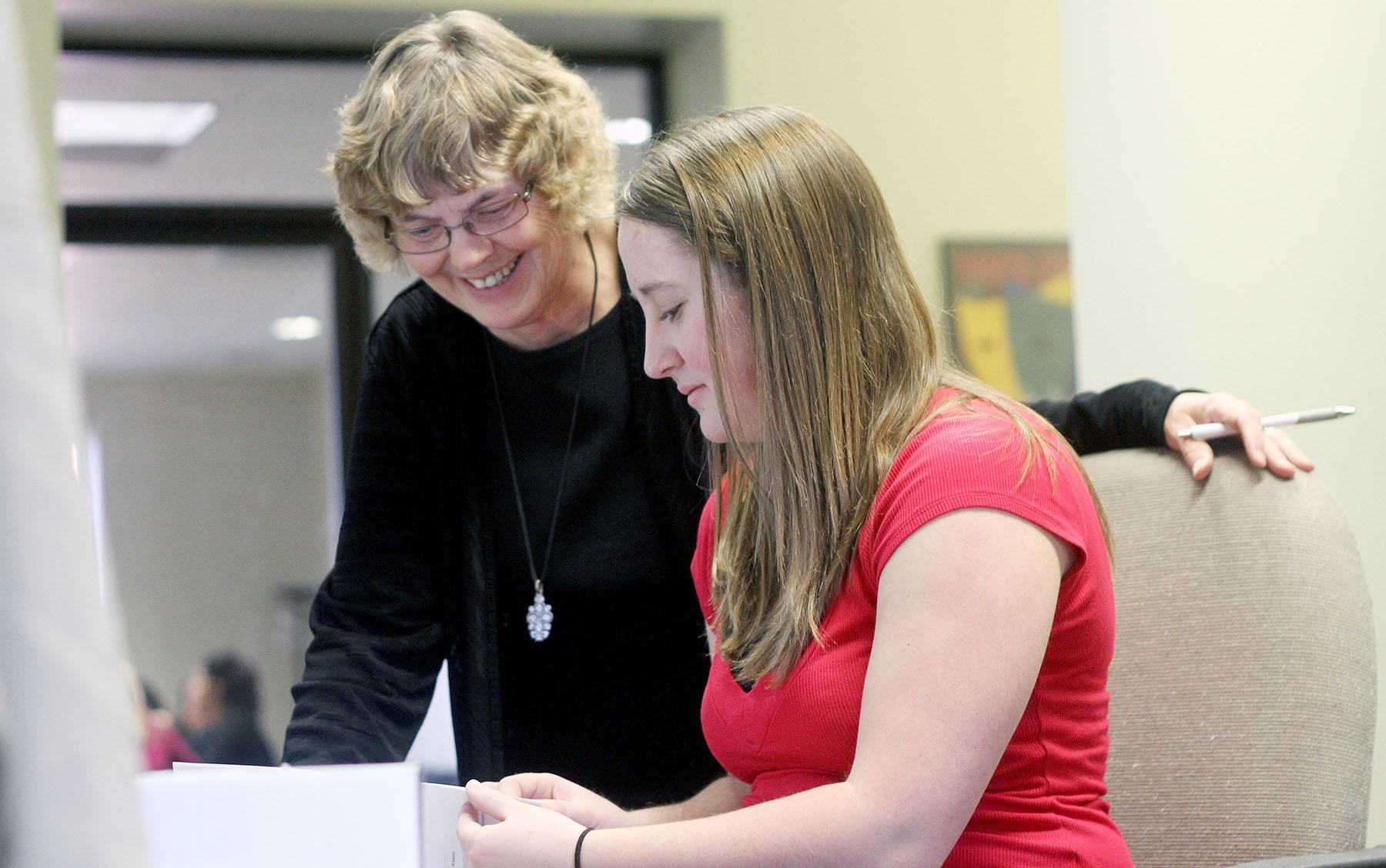 Junior Nakayla Lestina works with her internship supervisor Nancy Sturtevant Wednesday afternoon. Lestina is interning with the International Center.