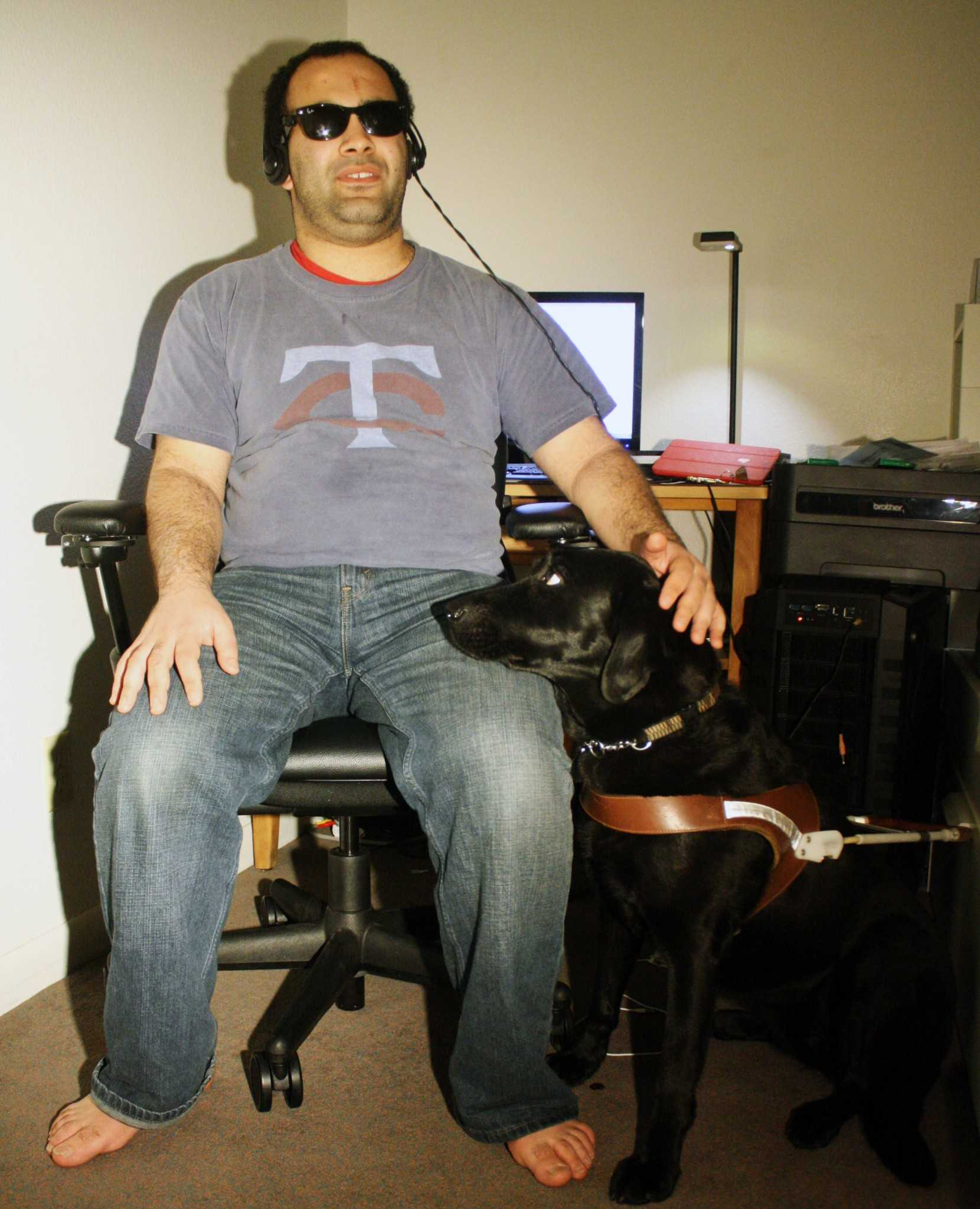 Noah Al Hadidi sits at his desk with his seeing-eye dog Amiga. A computer science major, Hadidi spends a lot of his time coding on his computer using specially modified equipment.