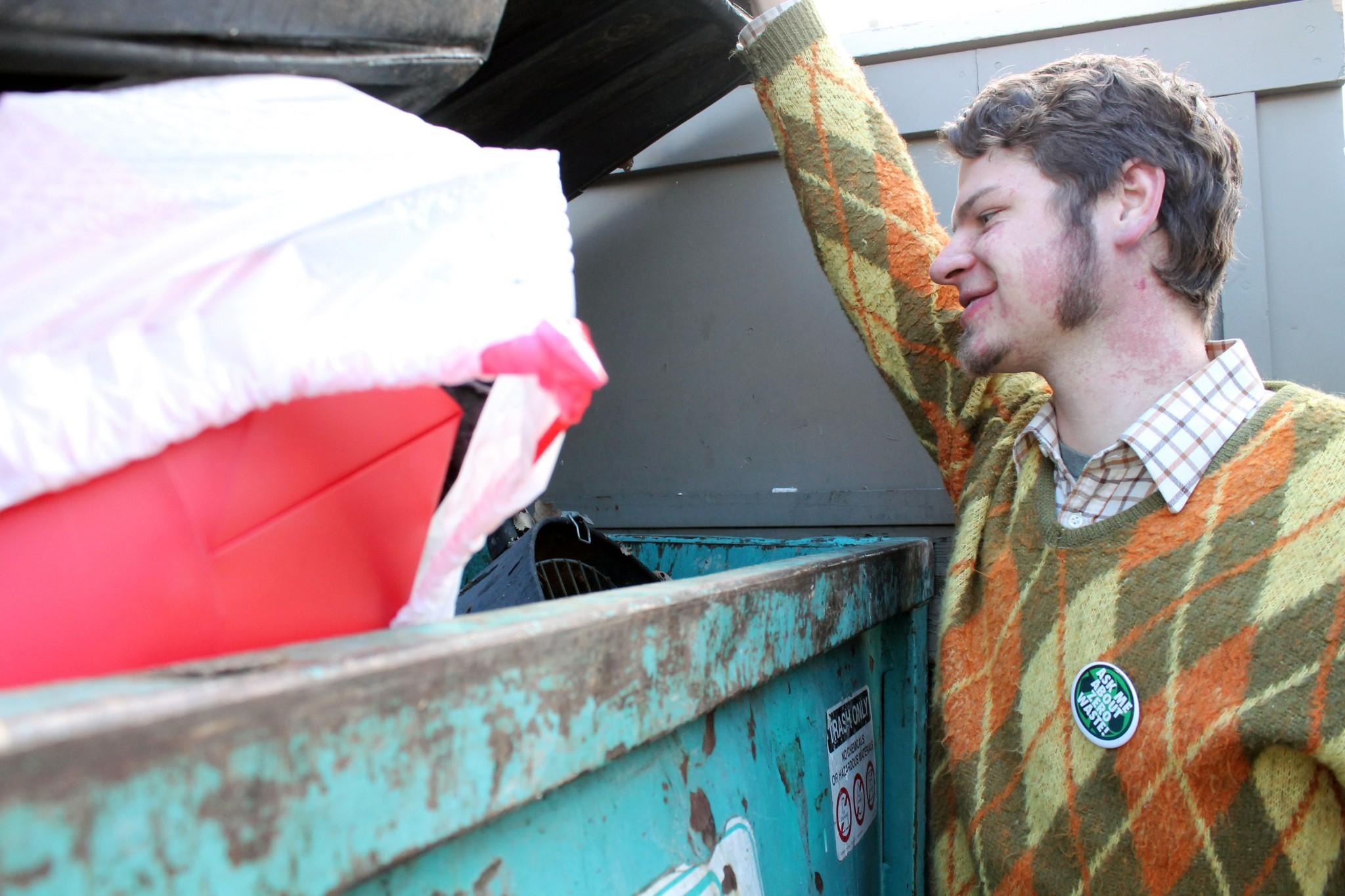 John Rooss, a soil and crop science major and organic agriculture minor, spots what will soon be his new fire pit in his neighborhood dumpster.  According to Rooss, in addition to using his findings for personal projects he also recycles and composts items that he finds.