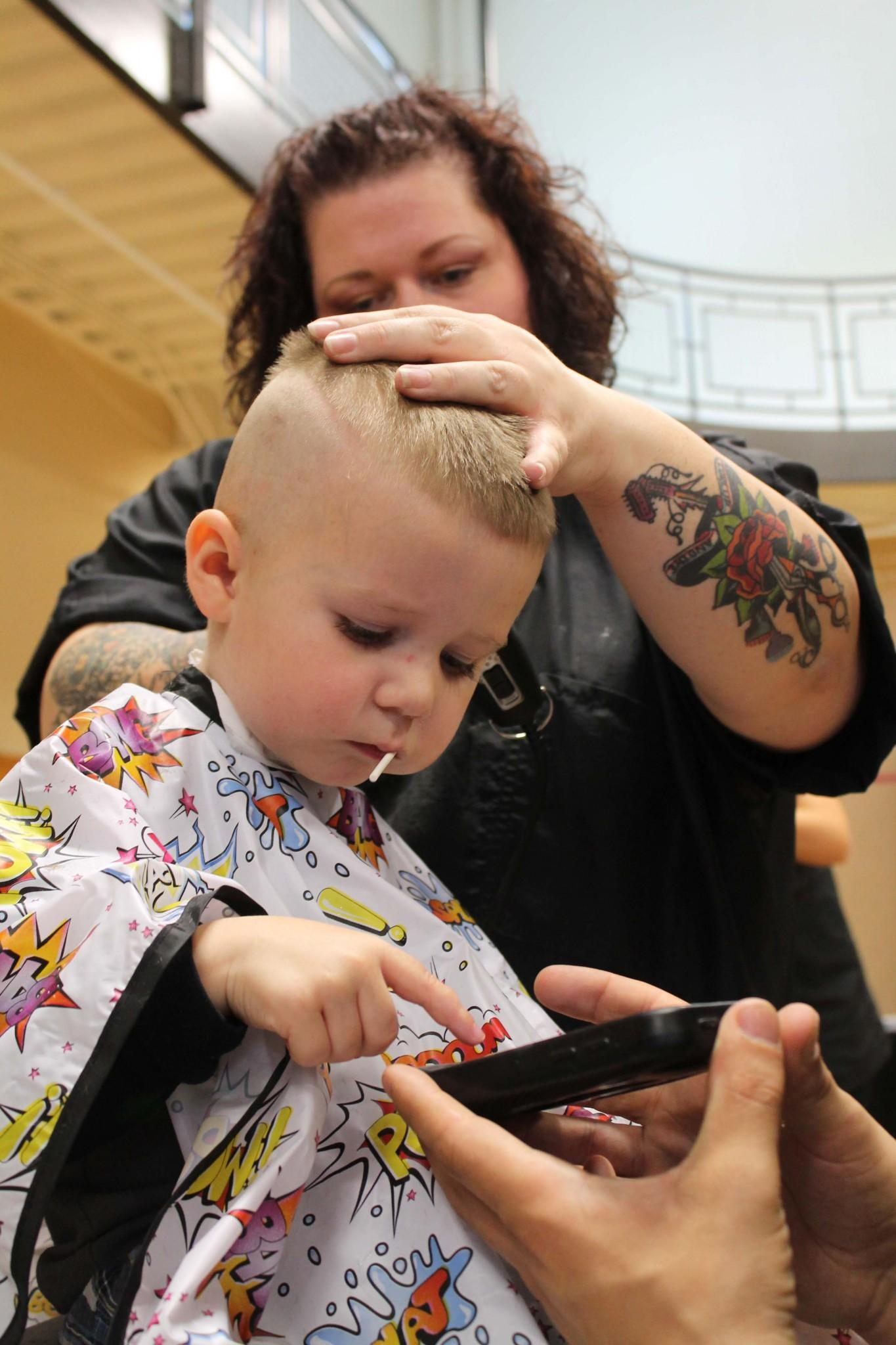Three year old Fort Collins resident, Gage, plays on his dad's phone while getting a hair cut at the Aztlan Community Center. Project Homeless Connect was a one day volunteering event that provided families in need with a variety of resources to help them get back on their feet.