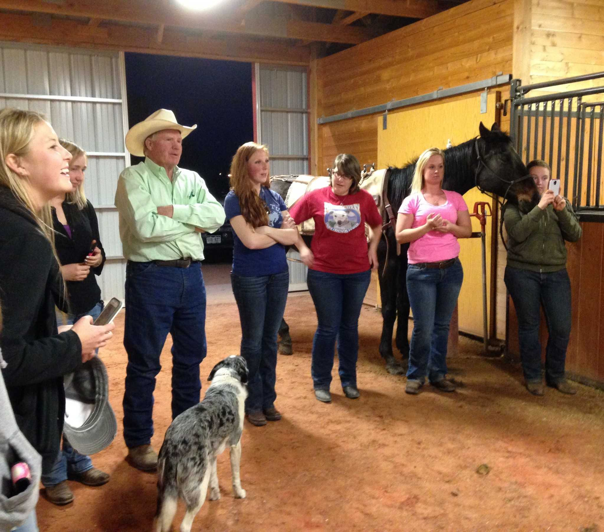 Mountain Rider Horse Club members and advisor Chuck Peterson, watch as Chuck directs the packing  demonstration. (Photo by Dixie Crowe)