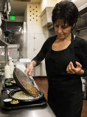 Maza Kabob co-owner and chef, Fariha Sayied, finishes off a hot plate of aashak, an Afghan dish, at Maza Kabob on Monday night. (Photo credit: Eliot Foust)