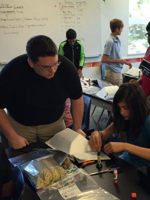 Engineering and teacher licensure student John Avery teaches a solar oven design activity which he modified to emphasize mathematical energy gain calculations. (Photo courtesy of Dr. De Miranda).