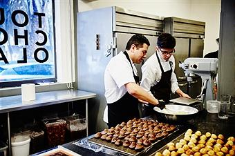 Chef supervising as baker preparing glaze for freshly baked goods in chocolate shop kitchen