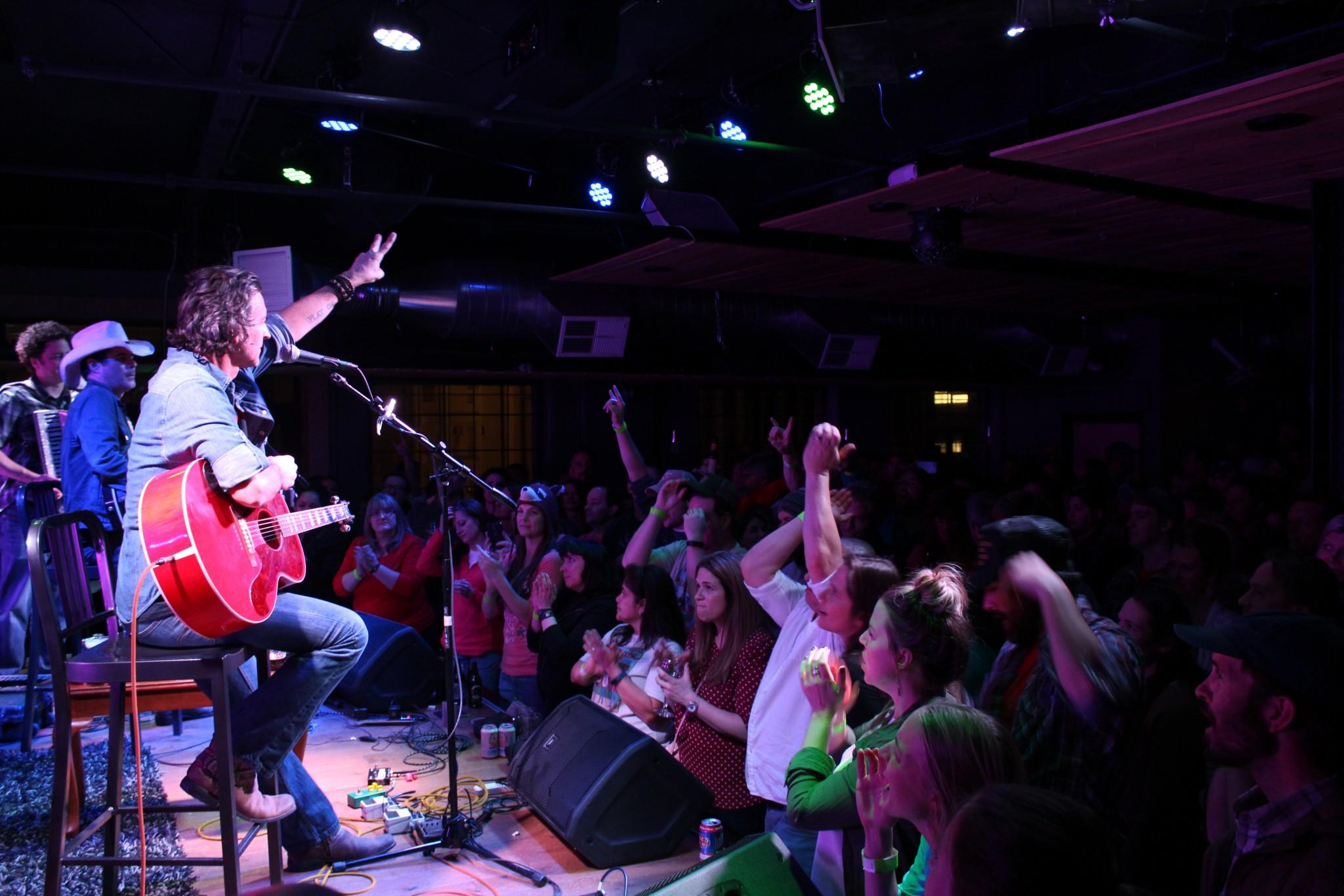 Roger Clyne does the peace sign to the crowd at the Downtown Artery, accompanied by Jim Dalton (center-stage) and Jeremy Lawton (far left)