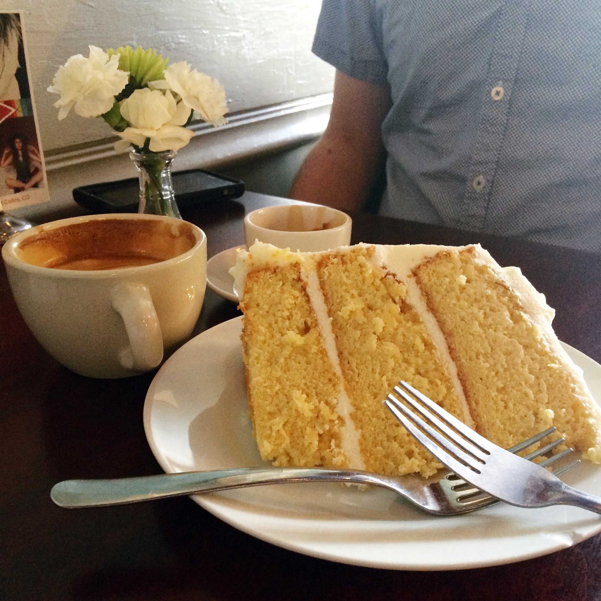 A slice of lemon cake along with a latte and an espresso. Photo by Rachael Worthington.
