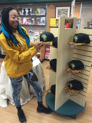 checks out the hats she designed in the CSU Bookstore. (Photo courtesy of Alexis Works.)