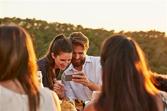 Smiling couple watching photographs on smart phone at dinner party