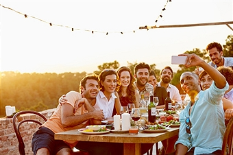 Smiling man taking group selfie on mobile phone at dinner party