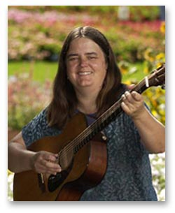 Ellen Audley playing guitar outside surrounded by flowers