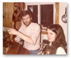 Curt Amason playing the upright bass and Ellen Audley playing the mandolin in a kitchen