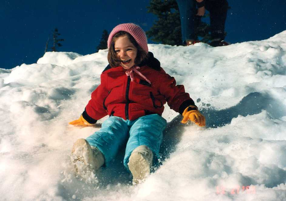 Amy slides down a hill while out with her family.