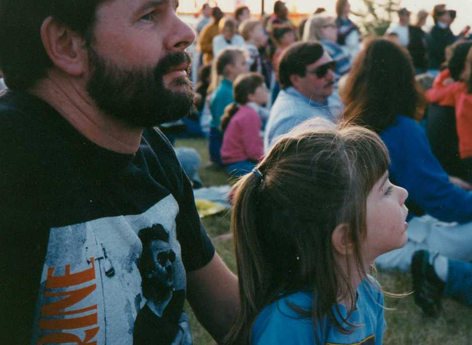 Amy and her dad watch a concert.