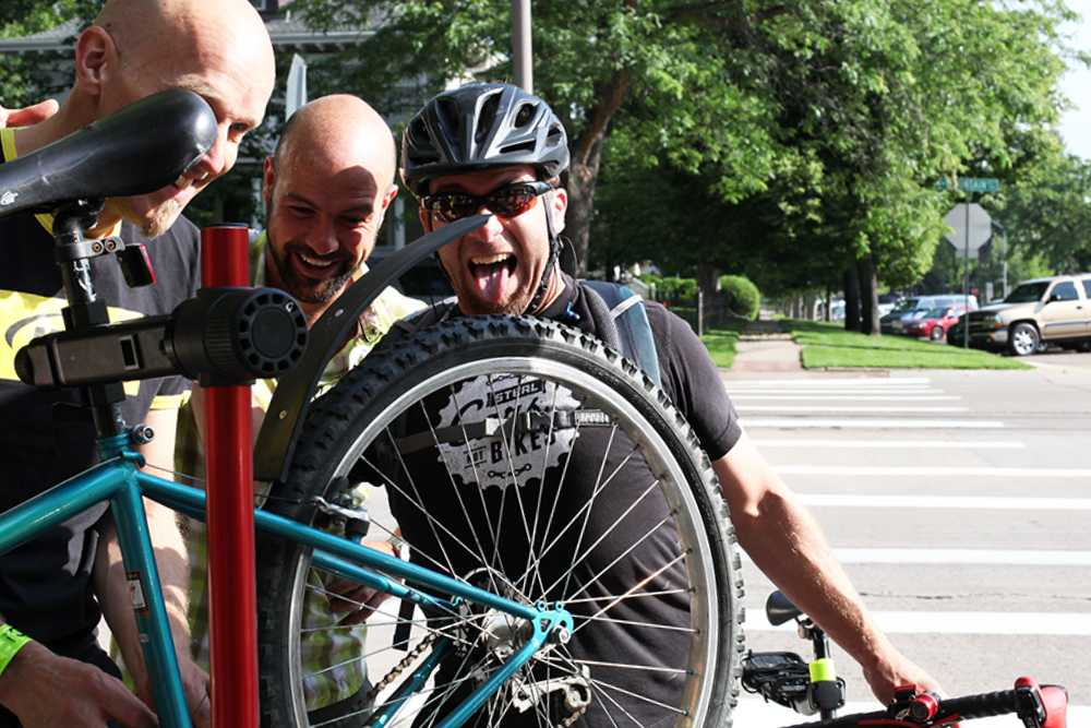 Bicyclists photobomb Marcel Van Garderen as he helps repair a bike.  Photo by Dina Alibrahim Fike.