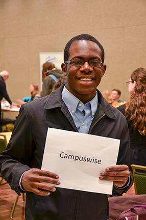 "Senior health and exercise science major, Jonathan James invites people to talk with him and learn more about Campuswise at Monday's Faith Fair. James said, ""it's all about community and about loving people and we really want to invite students to share with us in that love and community."""