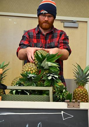 "Clark Cronfill carefully stacks pineapples on the Gathering at Faith table. Cronfill said ""We used pineapples to make people talk to us and remember us. No literal spiritual symbolism, but people do feel loved when we give them whole fruits."""