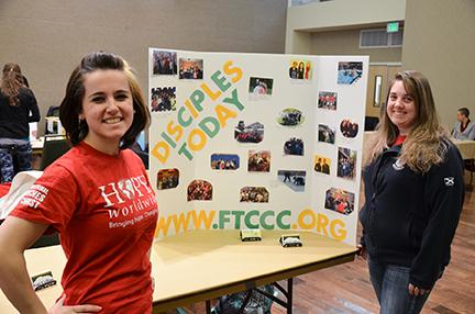 (From left) Lexy Bushue, freshman chemical engineering major and animal science junior Katrina Mulroy stand to promote Disciples Today at the Faith Fair Monday.