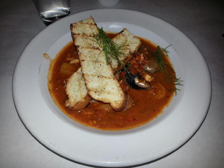 Cioppino is one of Jax Fish House & Oyster bar's Great Plates entree made with seasonal fish, clams, mussels, shrimp, tomato sofrito and topped with grilled bread.