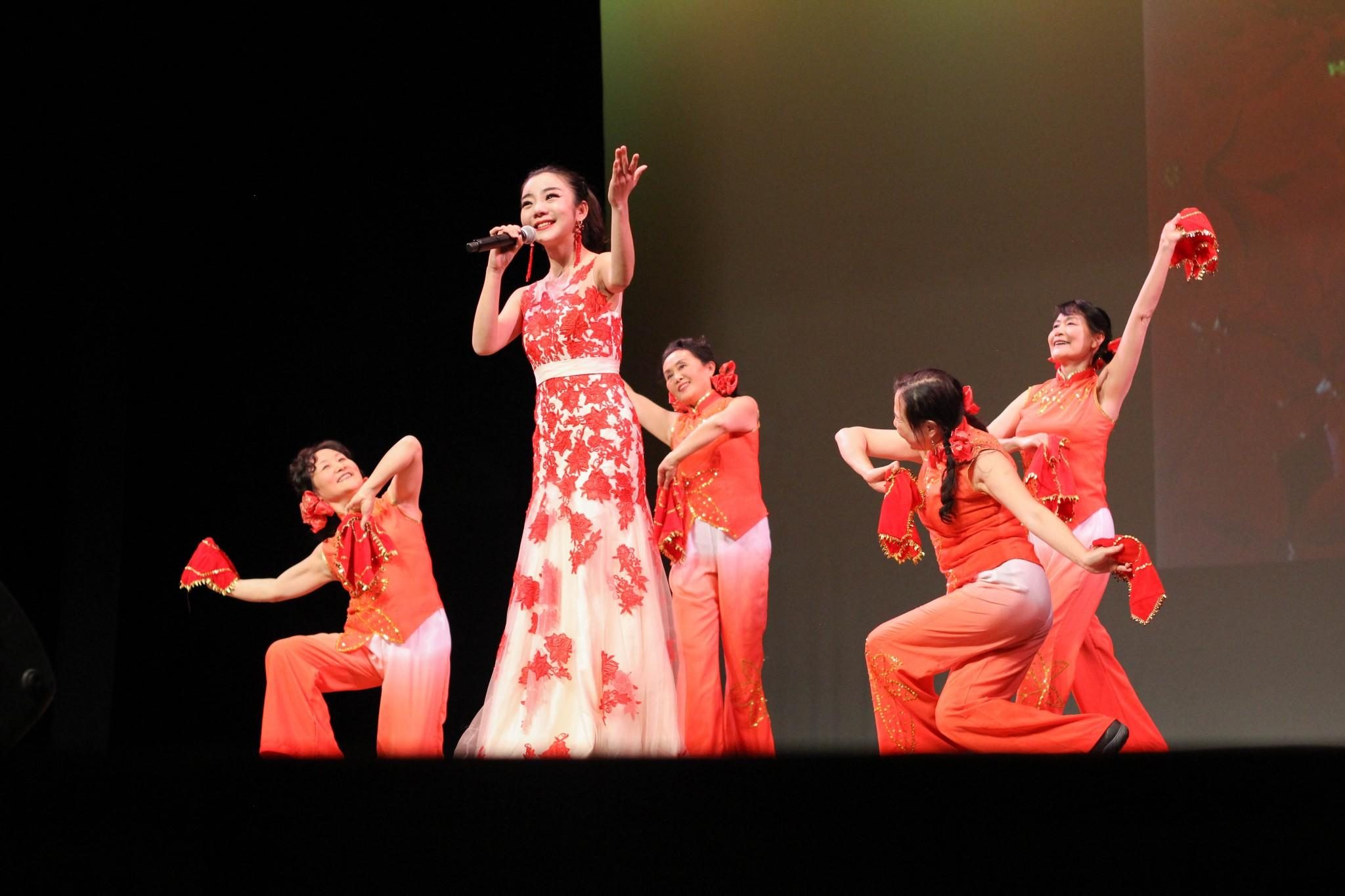 Cheng Xie performs a song in Mandarin at the 2016 Chinese Spring Festival Gala, accompanied by dancers Leyi Chen, Lin Zhang, Hong Wang and Yuexia Dou. The Fort Collins community gathered at the Lincoln center Sunday, Jan. 31. Photo by Jenna Fischer.