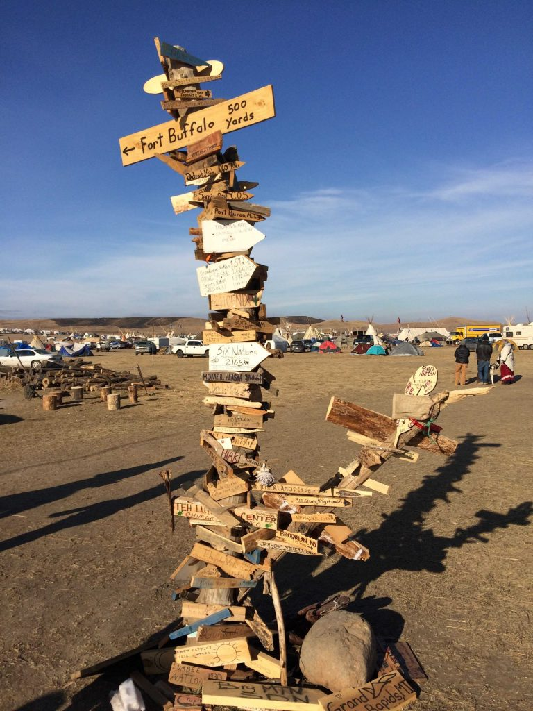 From near and far: A makeshift sculpture stands at the edge of the grounds near the river. It serves as a symbol of unity as people have traveled across states and nations to support the effort against the Dakota Access Pipeline. Photo by Alexandrea Rager