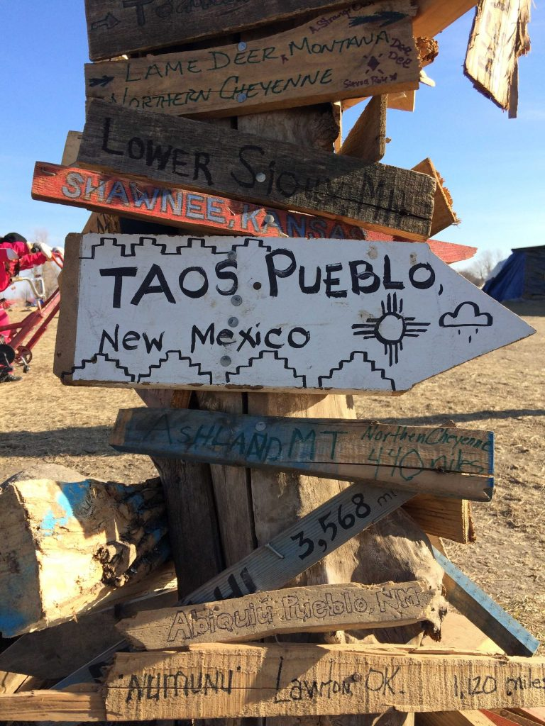 Support: Signs commemorate the distance people travel to arrive at the Sioux Sacred Rock Burial Grounds. Photo by Alexandrea Rager