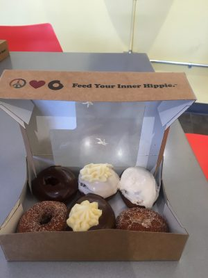 a half-dozen box of donuts including, peanut butter frosting, boston cream pie, two cinnamon sugar donuts, and a chocolate donut