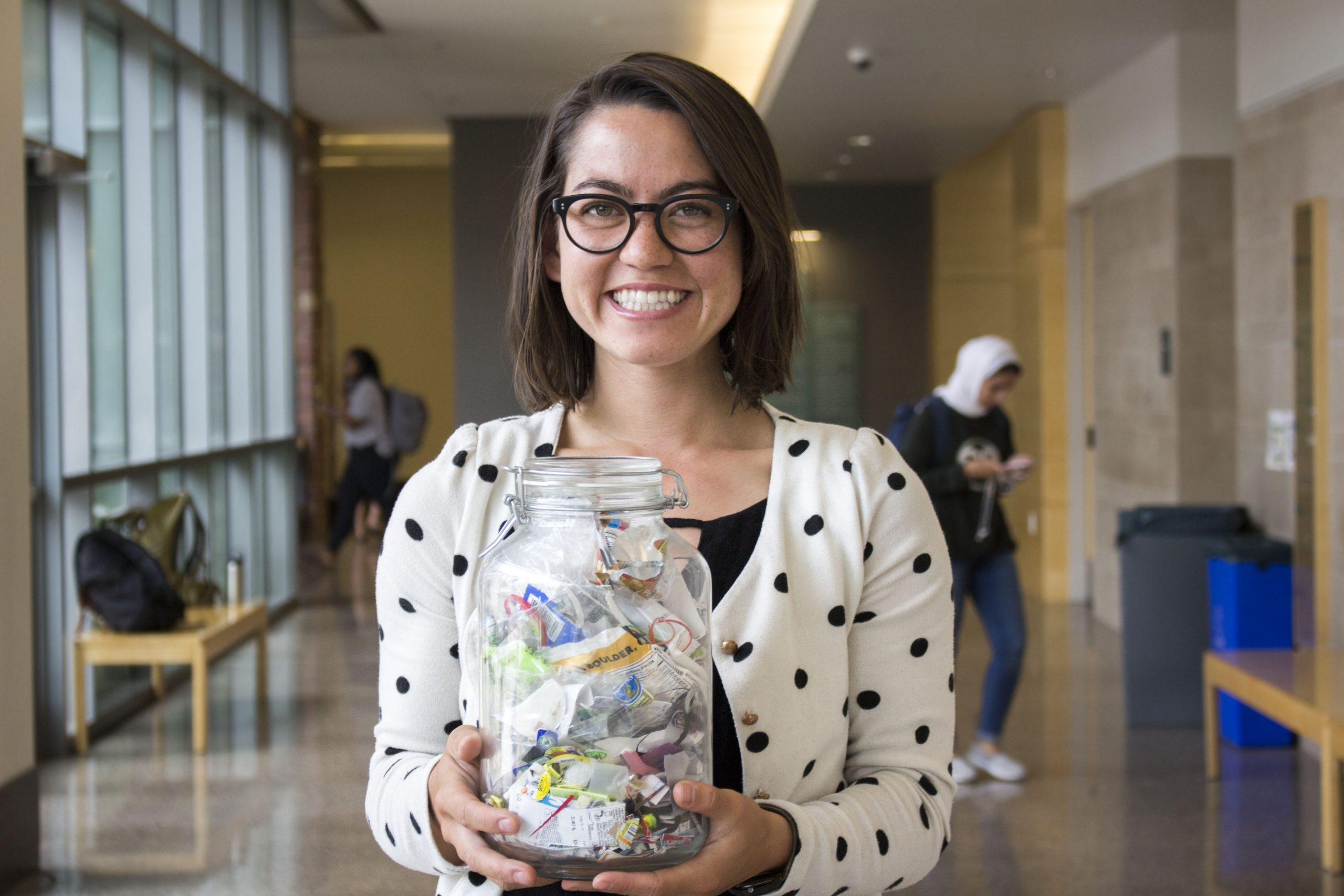 Marie Taylor, a senior Anthropology major, lives a minimal-waste lifestyle and holds a trash jar that contains all her nonrecyclable, noncompostable trash since January of this year.