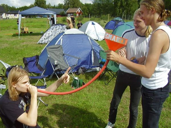 A man kneeling while his friend is holding a beer bong in a campground surrounded by tents.