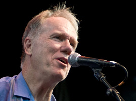 Loudon Wainwright III sings into a microphone