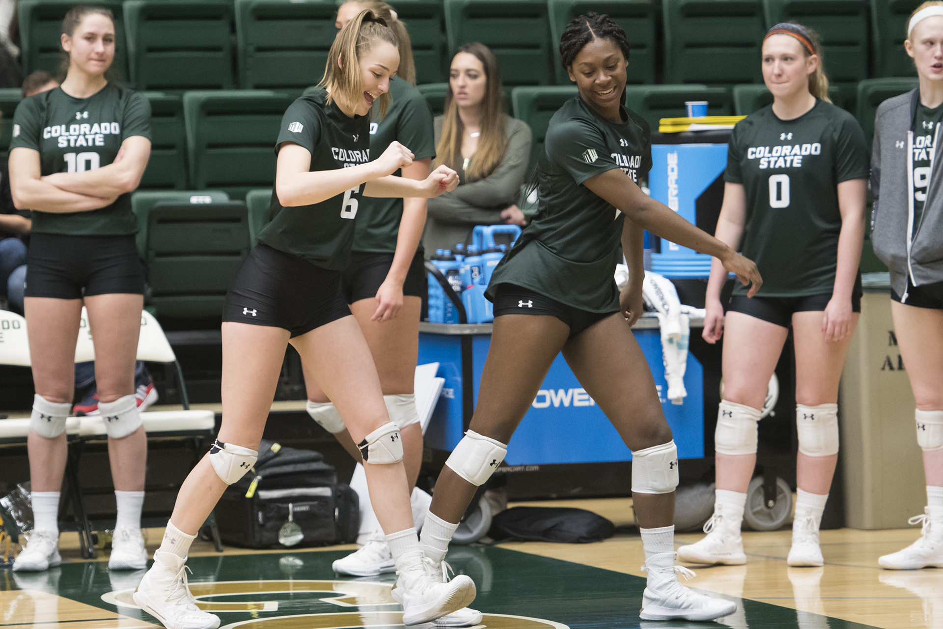 Freshmen Alana Giles and Madison Boles dance from the sideline while waiting for the first set to start.