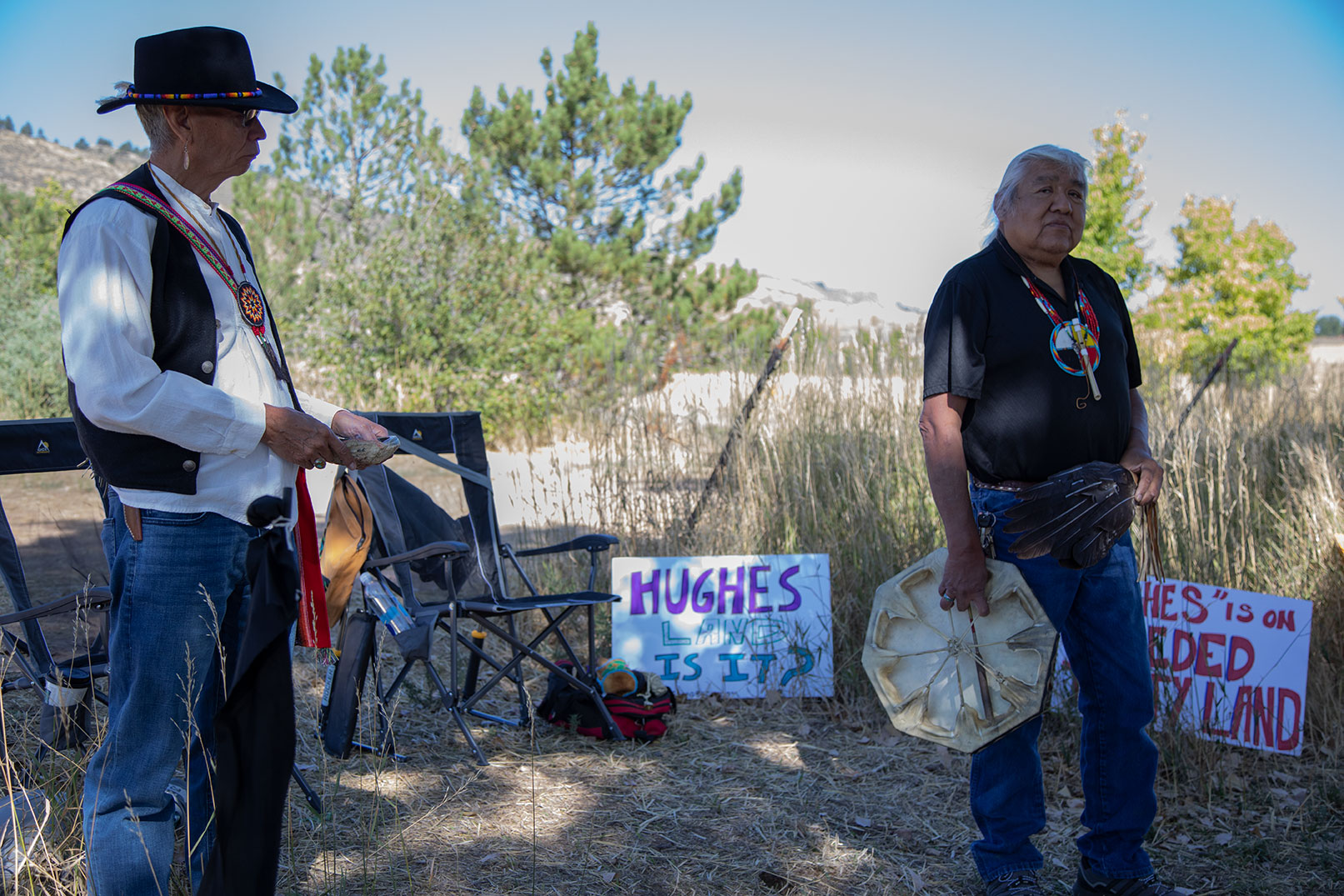 Two native men stand in the shade of the trees, talking to a group of people.